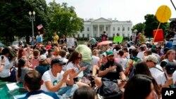 Los manifestantes se sientan en el suelo a lo largo de la avenida Pennsylvania, frente a la Casa Blanca en Washington, el sábado 29 de abril de 2017, durante la marcha