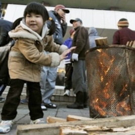 A girl warms herself at a shelter for quake-triggered tsunami survivors in Miyagi Prefecture.