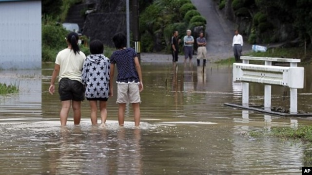Local girls walk in a flooded street due to typhoon Roke in Toyota, central Japan September 21, 2011.