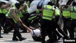 Un manifestante es arrestado por policías durante una protesta contra el presidente Nicolás Maduro.