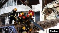 Petugas pemadam kebakaran menyelamatkan rekannya yang terkubur dalam reruntuhan bangunan yang ambruk saat berupaya memadamkan kebakaran di Harbin, provinsi Heilongjiang, China (2/1).
