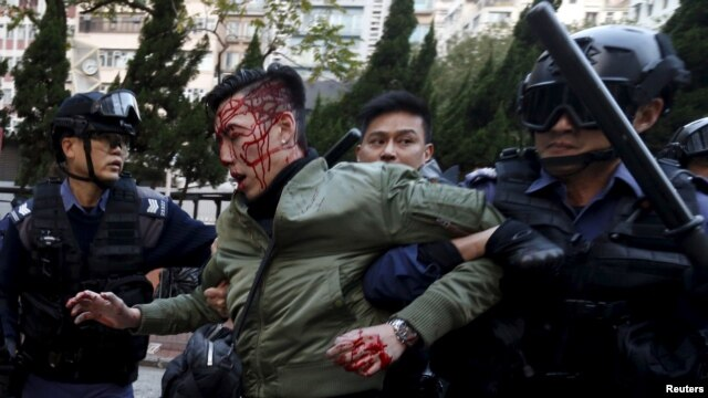 An unidentified injured man is escorted by riot police at Mongkok in Hong Kong, China February 9, 2016.