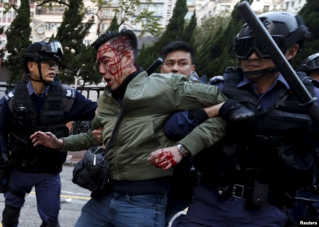 FILE - Riot police grip an unidentified injured man during protests in the Mongkok district of Hong Kong, Feb. 9, 2016.