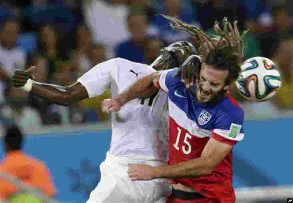 Ghana's Mohammed Rabiu, left, and United States' Kyle Beckerman struggle with each other to head the ball during the group G World Cup soccer match between Ghana and the United States at the Arena das Dunas in Natal, Brazil, Monday, June 16, 2014. (AP Ph
