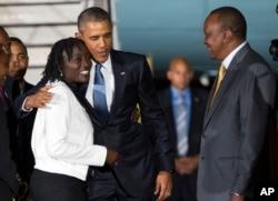 Kenyan President Uhuru Kenyatta, right, watches as President Barack Obama, center, hugs his half-sister Auma Obama, after he arrived at Kenyatta International Airport, on July 24, 2015, in Nairobi, Kenya.