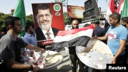 Palestinians carry trays of sweets and an Egyptian flag (C) in front of a placard depicting Egypt's Muslim Brotherhood's presidential candidate Mohamed Morsi in Gaza City, June 18, 2012.