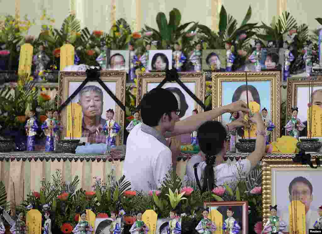 Relatives of passengers onboard the crashed TransAsia Airways plane offer joss sticks to the deceased at a funeral parlor on Taiwan's island of Penghu, July 24, 2014.