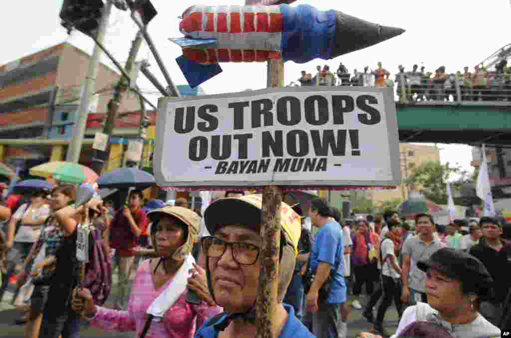 An activist holds a protest sign near the Malacanang Palace in Manila, Philippines, April 28, 2014.