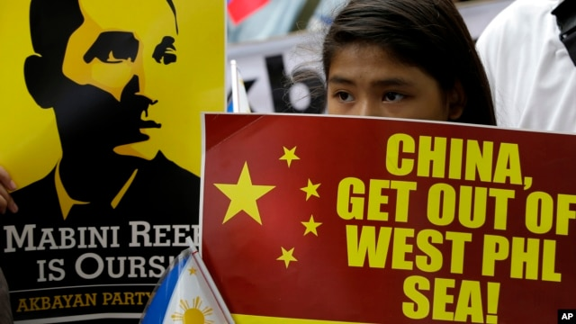 FILE - Protesters display a Philippine flag and placards while shouting slogans as they march towards the Chinese Consulate at the financial district of Makati city east of Manila.