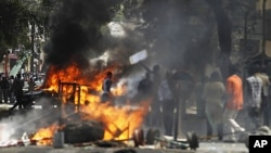 Anti-government protesters walk past a burning vehicle and barricades during a demonstration in the capital Dakar, June 23, 2011