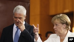 German Chancellor Angela Merkel, right, speaks as she gestures with Serbian President Boris Tadic, in Belgrade, Serbia, August 23, 2011