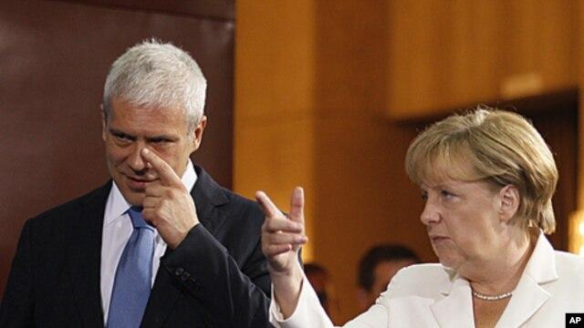 German Chancellor Angela Merkel, right, speaks as she gestures with Serbian President Boris Tadic, in Belgrade, Serbia, August 23, 2011