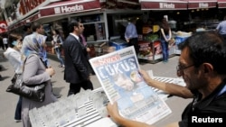 "A lottery ticket vendor reads a Turkish newspaper published with an headline reads ""downfall"" and a portrait of Turkey's President Tayyip Erdogan in Ankara, June 8, 2015."