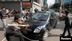 Activists of the Jamaat-e-Islami party vandalize a car upon hearing the revised sentencing of Abdul Quader Mollah, in Dhaka, Bangladesh, Sept. 17, 2013.