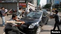 Aktivis partai Jamaat-e-Islami menyerang sebuah mobil sebagai protes atas keputusan MA yang menjatuhkan hukuman mati bagi Abdul Quader Mollah, pemimpin partai oposisi Jemaat-e-Islami, di Dhaka (17/9).