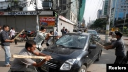 Activists of the Jamaat-e-Islami party vandalize a car upon hearing the revised sentencing of Abdul Quader Mollah, assistant secretary general of the party, in Dhaka September 17, 2013. Bangladesh's Supreme Court sentenced Mollah, an Islamist leader, to d