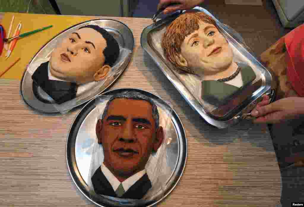 """Seniman Rusia Yelena Zelenskaya menunjukkan kue bergambar Kim Jong-Un, Barack Obama, dan Angela Merkel untuk persiapan pameran seni berjudul""""Sanksi yang Manis"""" diKrasnoyarsk, Siberia."""