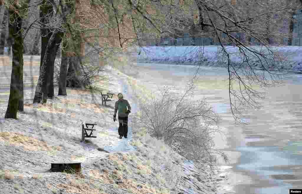 Seorang perempuan berjalan di sepanjang kanal di Stockholm, Swedia. Setelah cuaca hangat yang tidak biasa pada bulan Desember, Swedia mengalami suhu terdingin pada bulan Januari dalam lima belas tahun terakhir dengan suhu terendah -42.8º C di utara dan -15º C di Stockholm.