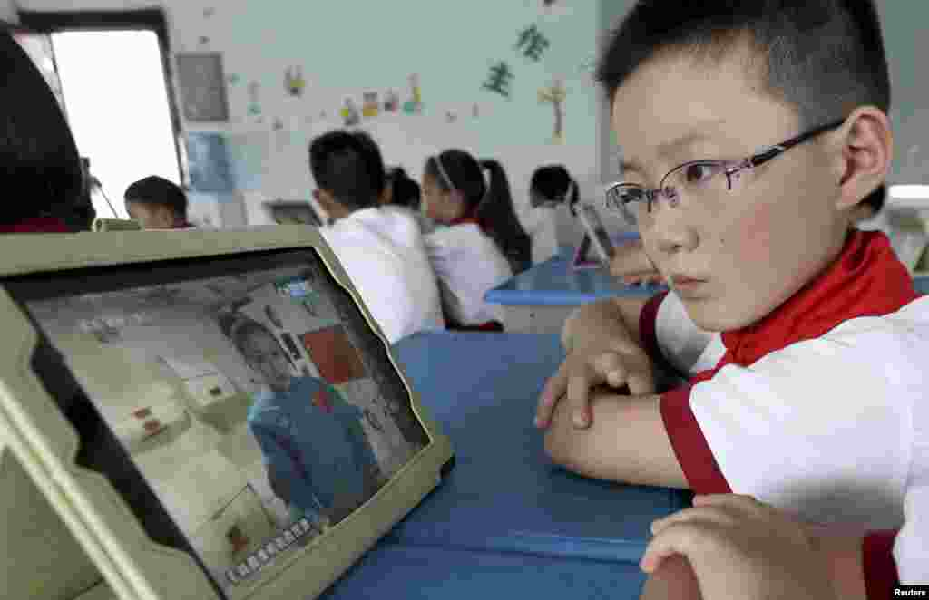 A student looks at his iPad at a primary school in Quzhou, Zhejiang province, China, as his class watches a live broadcast of a lecture given by Shenzhou-10 spacecraft astronauts on the Tiangong-1 space module.