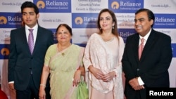 FILE - Mukesh Ambani (R), chairman of Reliance Industries Ltd, poses with his wife Nita (2nd R), mother Kokilaben (2nd L) and son Akash, before addressing the company's annual shareholders' meeting in Mumbai.