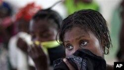 海地妇女用手绢蒙住鼻子和嘴,在医院里等待自己的孩子得到治疗