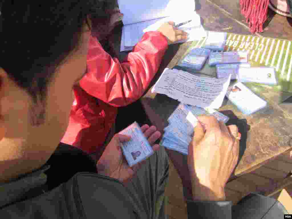An election worker gives out identification cards in Durbar Square, Kathmandu, Nov. 17, 2013. (Aru Pande/VOA)