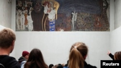 Visitors look at Gustav Klimt's Beethoven Frieze, one of the country's most famous artworks, at the Secession museum in Vienna, Oct. 16, 2013.