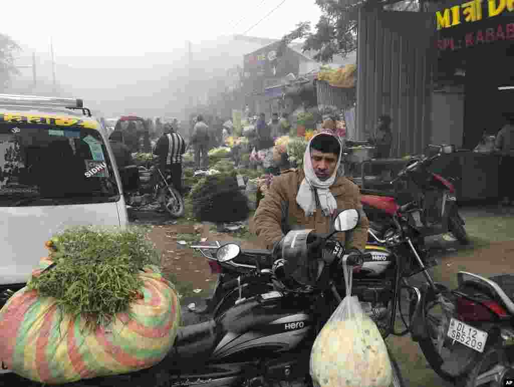 یک خرده فروش گل در صبح سرد و مه آلود دهلی نو گلهایی که از بازار خریده را روی موتورسیکلت خود جا میدهد.