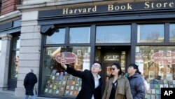 "Students pose for a selfie outside the Harvard Book Store, March 9, 2017, in Cambridge, Mass. Readers have been flocking to classic works of dystopian fiction. Some have shot to the top of best-seller lists, including George Orwell's ""1984"" and Margaret A"