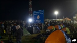 Migrants and refugees gather at a border crossing between Serbia and Hungary in Kelebija, Serbia, Thursday, Feb. 6, 2020. About two hundred migrants, including children, gathered Thursday at Serbia's border with Hungary to demand to be allowed entry…