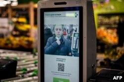 Perwakilan grup X5 mendemonstrasikan sistem pembayaran dengan teknologi pengenalan wajah di salah satu mesin kasir mandiri di supermarket Perekrestok di Moskow, 9 Maret 2021. (Foto: Dimitar DILKOFF / AFP)