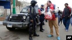 Des partisans du président égyptien Abdel Fattah al-Sissi donnant des fleurs aux policiers le 25 janvier 2016, lors de l'anniversaire du soulèvement populaire de 2011, sur la place Tahrir au Caire. (AP Photo/Amr Nabil)