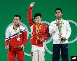브라질 리우올림픽에 출전한 북한 역도 국가대표팀 엄윤철 선수(왼쪽)가 남자 56kg급에서 은메달을 목에 걸었다. 금메달은 중국 룽칭취안(가운데) 선수에게 돌아갔다.