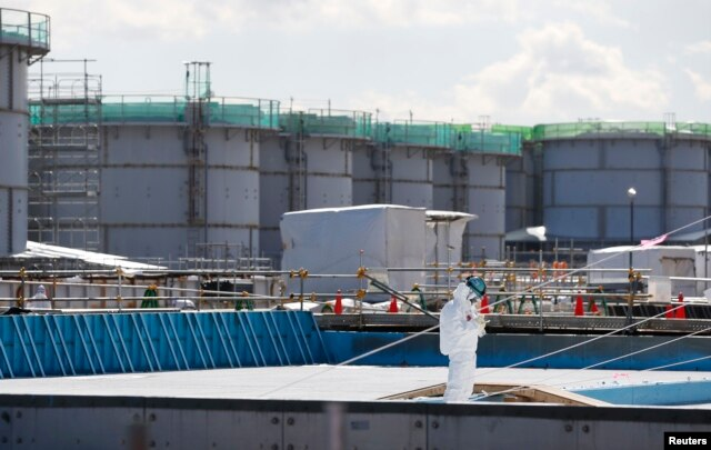 FILE - A worker, wearing protective suits and masks, takes notes in front of storage tanks for radioactive water at Tokyo Electric Power Co's (TEPCO) tsunami-crippled Fukushima Daiichi nuclear power plant in Okuma town, Fukushima prefecture, Japan, Feb.10, 2016.
