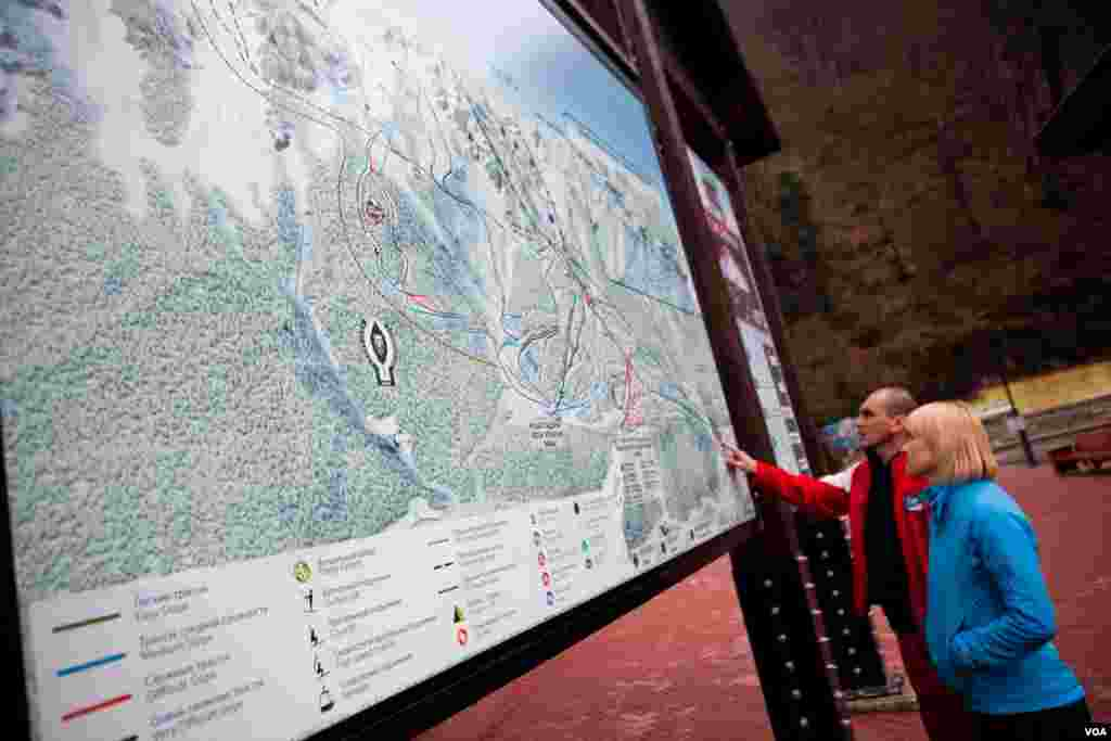 Visitors study the ski trail map of Rosa Khutor, which suffered from erratic snow cover and rain in February and March of this year. (V. Undritz for VOA)