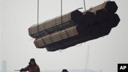 在中国唐山曹妃甸港口,工人把钢管装船。(2012年2月20日)中国钢铁业产能严重过剩