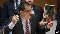 Venezuela Foreign Affairs Minister Jorge Arreaza shows picture he said represent opposition members initiating violence, during a meeting on Venezuela in the Security Council at U.N. headquarters, Feb. 26, 2019.