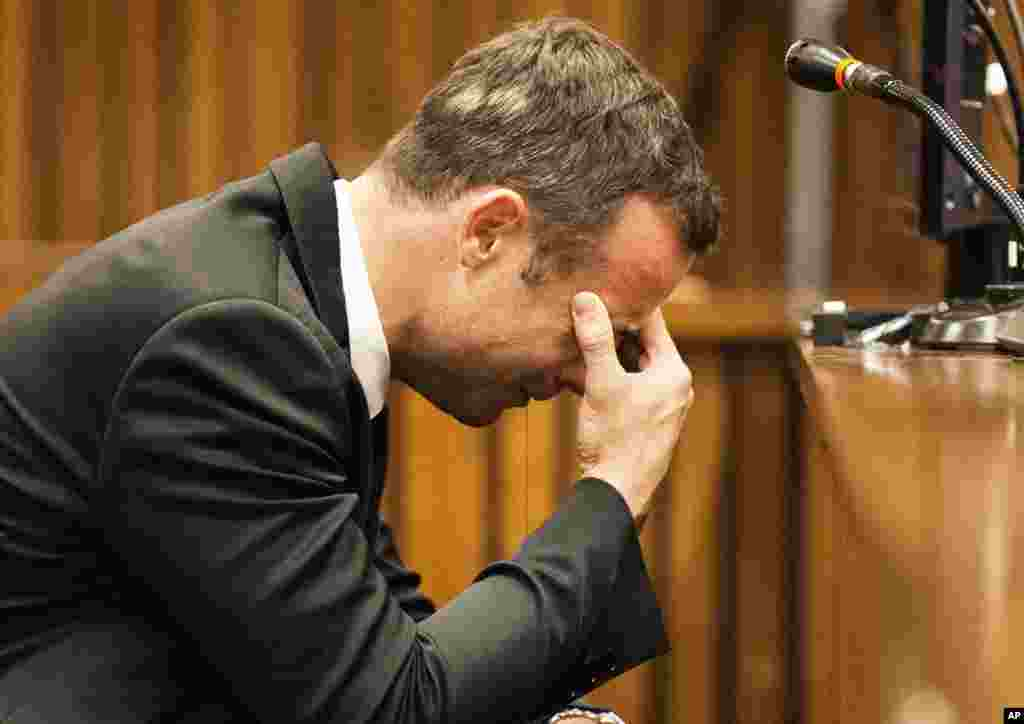 Oscar Pistorius puts his hand to his face while listening to evidence from a witness speaking about the morning of the shooting, Pretoria, March 6, 2014.