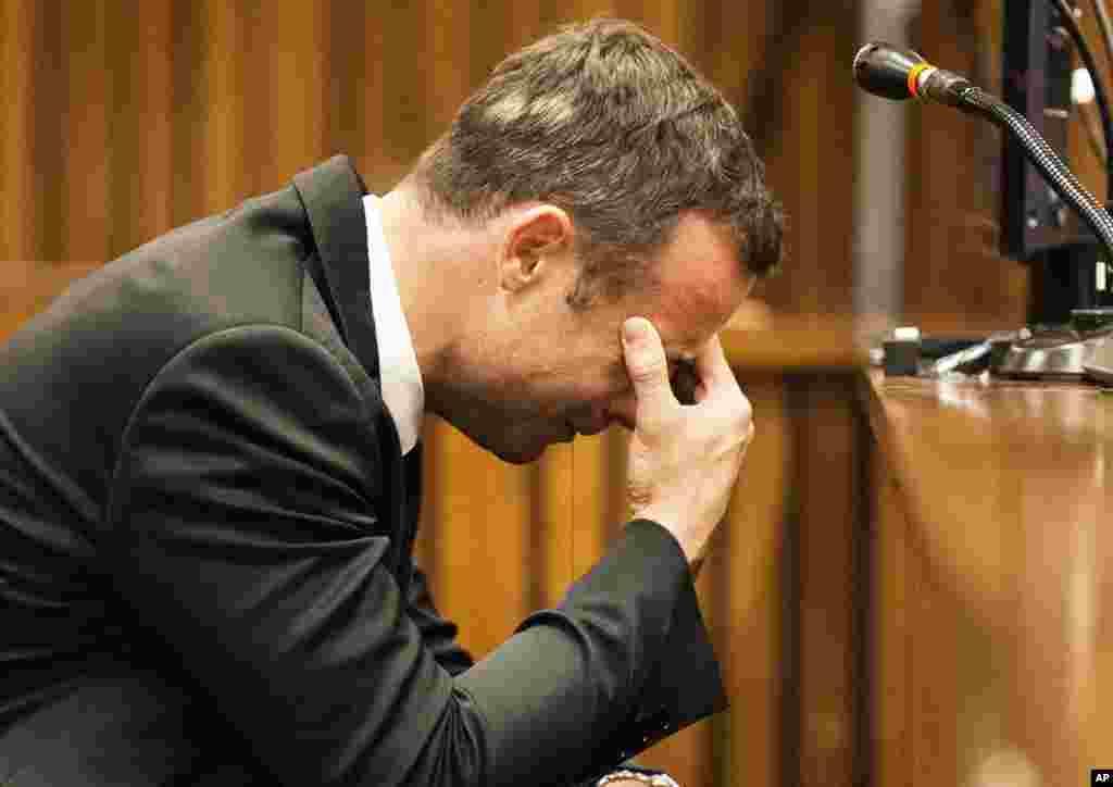 Oscar Pistorius leva a mão à cara enquanto ouve o depoimento de uma das testemunhas que relata a manhã do tiroteio, no quarto dia de julgamento no tribunal de Pretória, Março 6, 2014.