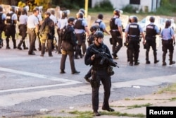 Police line up to block the street as protesters gathered after a black man was shot by police serving a search warrant in St. Louis, Missouri, Aug. 19, 2015.