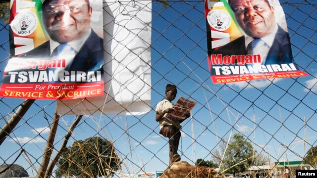 A Zimbabwean opposition party Movement For Democratic Change (MDC) supporter holds a party newsletter at an election rally about 90 km (56 miles) east of the capital Harare, Zimbabwe, July 23, 2013.