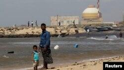 一名男子和他的兒子站在印度南部的泰米爾納德邦庫丹庫拉姆核電項目前的海灘。