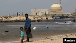 FILE - A man stands with his son on the beach near the Kudankulam nuclear power project in the southern Indian state of Tamil Nadu.