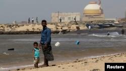 一名男子与他的儿子站在印度南部泰米尔纳德邦的库丹库拉姆核电站附近(资料照片)