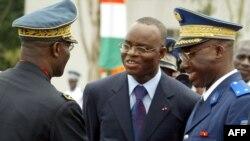 Le ministre de la Défense de la Côte d'Ivoire Moïse Lida Kouassi, au centre, rencontre le général en chef de l'armée Mathias Doue, à gauche, et le chef de la gendarmerie Touvoly, à droite, lors des célébrations pour l'indépendance du pays, le 07 août 200