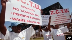 FILE: Members of the Zimbabwe Congress of Trade Unions hold banners advocating for the scrapping of taxes on pension benefits.Hundreds of workers converged in Harare, Sunday, May, 1, 2005, to celebrate International Workers Day. (AP Photo)