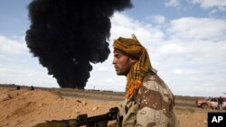 ກຳລັງຕໍ່ຕ້ານຄົນນຶ່ງ ທີ່ມີປືນຍິງຈະຫຼວດໝາກປີ RPG ເປັນອາວຸດ ໃນລະຫວ່າງການປະທະກັນ ກັບກຳລັງນິຍົມ Gadhafi ໃກ້ໆເມືອງ Ras Lanuf ແລະເມືອງ Bin Jawad (9 ມີນາ 2011)