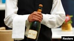 """Un serveur ouvre une bouteille de champagne """"Trump"""" à l'hôtel Trump International le jour de son ouverture à Washington, aux États-Unis, le 12 septembre 2016."""