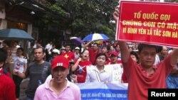 Người biểu tình cầm biểu ngữ chống Trung Quốc tuần hành qua đường phố Hà Nội, ngày 1/7/2012