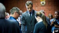 FILE - Oscar Pistorius cries as he prays with his sister Aimee and brother Carl in the magistrates court in Pretoria, South Africa, Aug. 19, 2013.